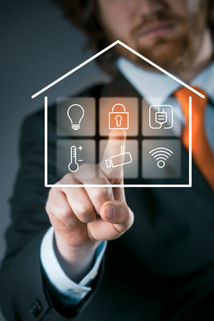 Photo pour Businessman using a smart house control panel activating the security setting on a transparent virtual interface - image libre de droit