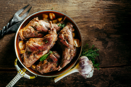 Photo for High Angle View of Roasted Rabbit Haunches in Pan with Stewed Vegetables on Rustic Wooden Table Surface with Bulb of Garlic and Copy Space - Royalty Free Image