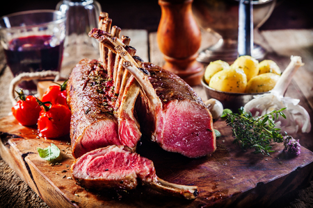 Foto für Rare Rectangle Rack of Lamb on Wooden Cutting Board Surrounded by Fresh Herbs and Ingredients - Lizenzfreies Bild