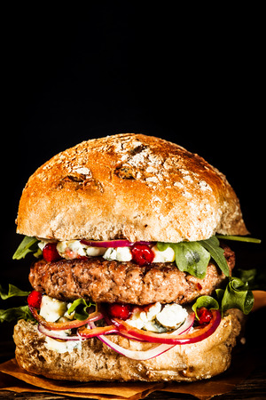 Foto de Close Up of Single Healthy Looking Burger Piled with Fresh Vegetables and Cheese on Whole Grain Bun, on Black Background with Copy Space - Imagen libre de derechos