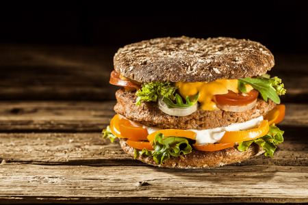 Foto de Single Healthy Looking Burger Piled with Fresh Vegetables and Sauces on Whole Grain Bun, on Rustic Wooden Surface with Copy Space - Imagen libre de derechos