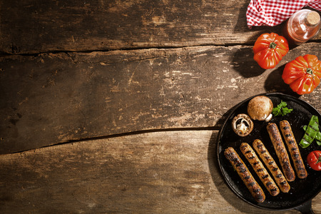 Foto de Grilled barbecued sausage with portobello mushrooms and fresh tomato on an old rustic wooden with cracks viewed from above, copyspace - Imagen libre de derechos
