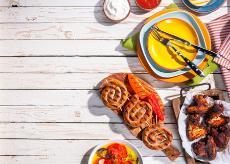 Photo pour High Angle View of Grilled Sausages and Chicken Wings on Picnic Table with Colorful Plates and Cutlery, Copy Space on Table with Barbequed Meal - image libre de droit