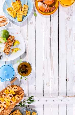 Photo pour High Angle View of Grilled Fruit and Seafood Dishes Scattered on White Wooden Table Surface with Copy Space - image libre de droit
