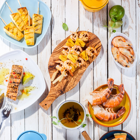 High Angle View of Grilled Fruit and Seafood Dishes Arranged on White Wooden Table Surface