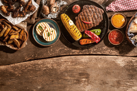 Photo for High Angle View of Grilled Meal of Steak, Chicken and Vegetables Spread Out on Rustic Wooden Table at Barbeque Party - Royalty Free Image