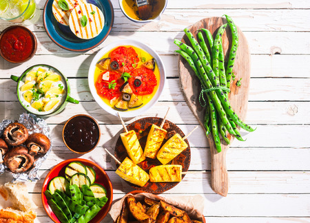 Photo pour High Angle View of Vegetarian Mediterranean Meal of Grilled Fruit and Vegetables Spread Out on White Wooden Picnic Table with Copy Space - image libre de droit
