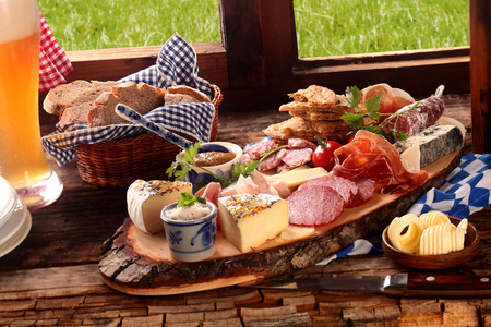 Foto de Delicious midday meal of a meat and cheese platter with a wide variety of cheeses, spicy sausage and ham served with a cold beer and fresh bread in a Bavarian tavern - Imagen libre de derechos