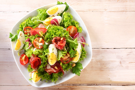 Photo pour High Angle View of a Nutritious Vegetable Salad with Boiled Egg Slices, Served on a White Plate on Top of a Wooden Table - image libre de droit