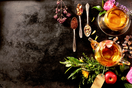 Photo for Overhead view of various sorts of tea. Flavoured with Assorted Herbs, an apple, rose with a teapot and a teacup on a rustic black metal board - Royalty Free Image