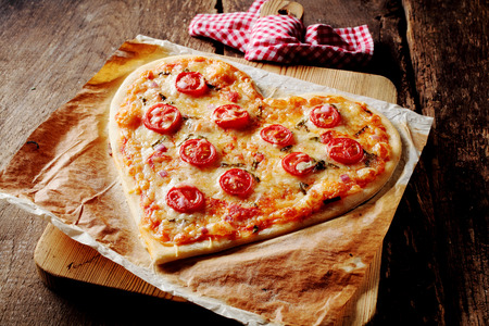 Foto de Baked heart-shaped homemade pizza topped with mozzarella and tomato slices, on parchment paper on a cutting board near a checkered red and white kitchen towel, on a rustic table, high-angle close-up - Imagen libre de derechos