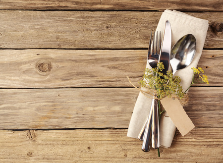 Photo for High Angle View of Cutlery Tied on White Napkin with Small Leaves on Stem and Empty Brown Tag, Placed on Wooden Table with Copy Space. - Royalty Free Image