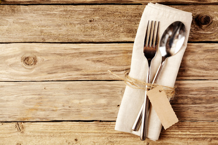Foto de High Angle View of Spoon and Fork Tied on a White Napkin with Empty Tag, Placed on Wooden Table with Copy Space. - Imagen libre de derechos
