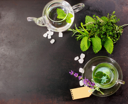 Foto de Freshly brewed peppermint tea with fresh herbal ingredients and flowers alongside in a glass cup and teapot for a refreshing healthy drink, overhead view on slate with copyspace - Imagen libre de derechos