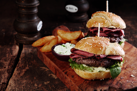 Photo pour Gourmet Tasty Steak Burgers with Ham Slices on a Wooden Tray with Potato Wedges and Dipping Sauce. - image libre de droit