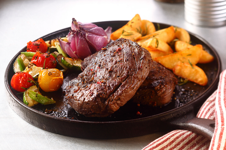 Photo for Close up Gourmet Appetizing Roasted Beef Steak with Potato Wedges and Other Vegetables on a Cast Iron Skillet. - Royalty Free Image