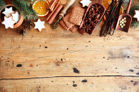 Photo for Traditional Christmas spices and cookies arranged as a top border over rustic wood background with cinnamon, star anise, speculoos and star biscuits and dried orange slices, large copyspace - Royalty Free Image