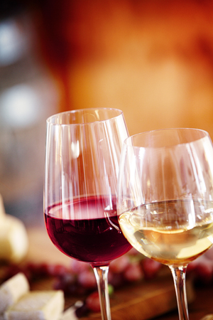 Photo pour Glasses of red and chilled white wine on a dining table with background blur copyspace, close up view of the beverage - image libre de droit