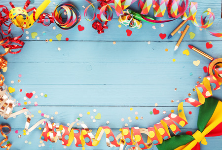 Photo for Festive party border or frame of colorful spiral streamers and confetti arranged on a rustic old blue wooden background with a bow tie in the corner and copyspace - Royalty Free Image