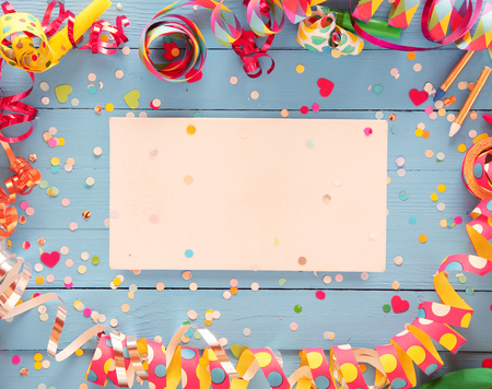 Photo for Decorative party frame of colorful spiral streamers and confetti over a rustic blue wood background with central blank card with copyspace for your greeting or invitation - Royalty Free Image