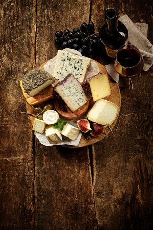 Photo for Gourmet cheese platter with a wide variety of soft creamy and semi-hard cheeses as well as gourmet speciality varieties, viewed high angle on a rustic wooden table with copyspace - Royalty Free Image