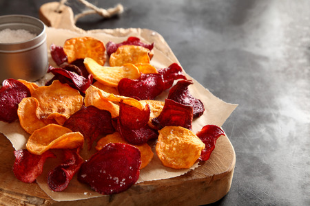 Photo for Crisp crunchy organic vegetable chips with fried or oven-baked potato and beetroot chips served as a finger food snack on a wooden chopping board with sea salt and copyspace - Royalty Free Image