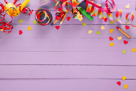 Photo for Colorful festive party border and background with with vibrant multicolored streamers, matches and confetti on a rustic lilac wood background with copyspace for your greeting or invitation - Royalty Free Image
