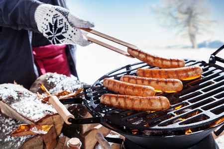Foto de Outdoors winter barbecue party with a person wearing knitted woollen gloves cooking sausages over hot coals in a BBQ, close up view - Imagen libre de derechos