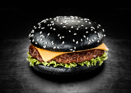 Photo pour Japanese Black Burger with Cheese. Cheeseburger from Japan with black bun on dark background - image libre de droit