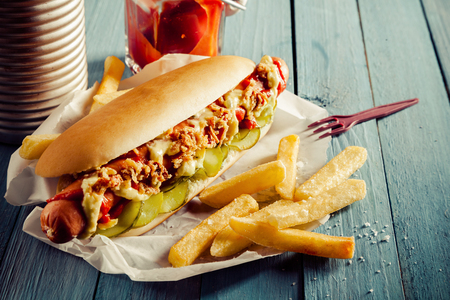 Photo for Tasty hot dog with a smoked frankfurter sausage covered with full trimmings on a bed of cucumber on a fresh roll with golden crispy fried potato chips and relish or ketchup on a rustic wooden table - Royalty Free Image
