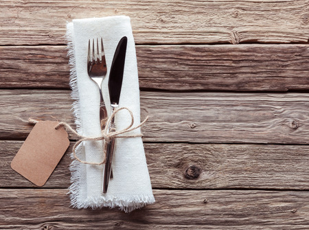 Foto de High Angle View of Silver Knife and Fork Tied with String and Blank Tag on White Napkin with Fringed Edges on Rustic Wooden Table with Copy Space - Imagen libre de derechos