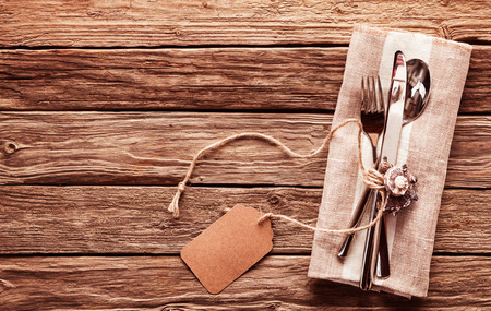 Foto de High Angle View of Set of Silver Cutlery Tied with String and Blank Tag on Natural Colored Napkin on Rustic Wooden Table with Copy Space - Imagen libre de derechos