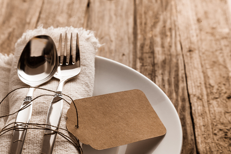 Foto de Rustic Christmas place setting with a knife and for on a beige napkin with a blank brown gift tag arranged on a side plate on a wooden table, close up high angle - Imagen libre de derechos