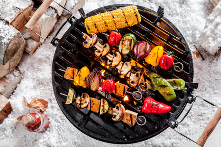 Photo pour Overhead view of colorful vegetable kebabs and a corncob grilling on a winter BBQ outdoors in snow with tasty spicy dips and the wood pile alongside - image libre de droit