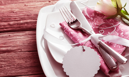Foto de Blank Tag Tied Around Silver Knife and Fork Resting on Pink Napkin on top of White Dishes and Decorated with White Rose and Small Pearl Hearts - Romantic Wedding Place Setting with Copy Space - Imagen libre de derechos