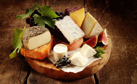 Foto de Gourmet cheese platter on a rustic buffet with a large assortment of tasty regional and speciality soft and semi-hard cheeses displayed with fresh grapes and figs, close up view - Imagen libre de derechos