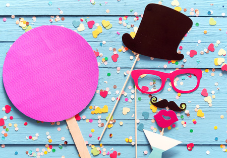 Foto de Party fun with photo booth accessories arranged as a gent in a top hat with a mustache sipping cocktails with a magenta circle with copy space alongside for your invitation or greeting - Imagen libre de derechos