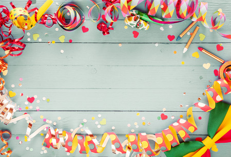 Foto de Colorful party frame with streamers and confetti and a vibrant bow tie in a corner around central copy space on a rustic wooden background - Imagen libre de derechos