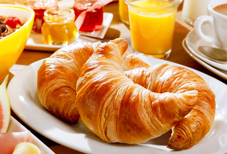 Photo for Delicious continental breakfast with fresh flaky croissants, assorted preserves, orange juice , cereal and coffee, close up on the croissants - Royalty Free Image