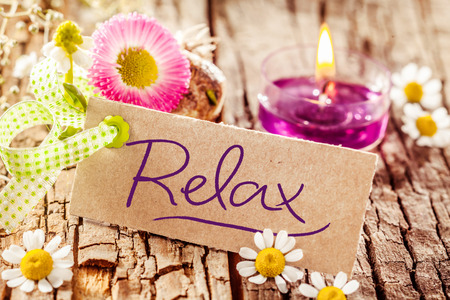 Foto de Cute relaxation display with handwritten relax sign set on tree bark surface decorated with various flowers and candle - Imagen libre de derechos