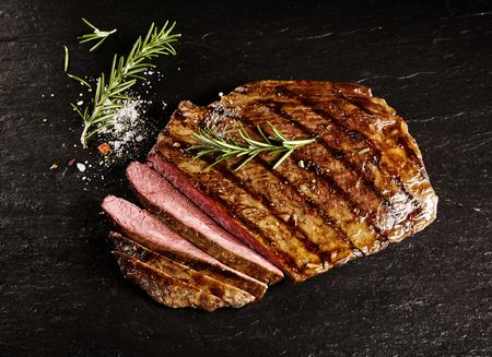 Foto de Single roasted medium rare sliced flank beef piece with rosemary over dark table background - Imagen libre de derechos