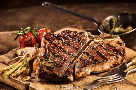 Prepared grilled large t-bone steak surrounded by tomatoes and garnished with seasonings next to fork and knife on cutting board