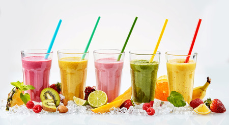 Photo for Five large glasses of red yellow pink and green tropical fruit smoothies with colorful straws standing in crushed ice beside cut fruit - Royalty Free Image