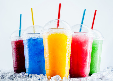 Foto de Still Life Profile of Frozen Fruit Slush Granita Drinks in Plastic Take Away Cups with Lids and Drinking Straws Chilling on Cold Metal Surface with Scattered Ice Cubes - Imagen libre de derechos