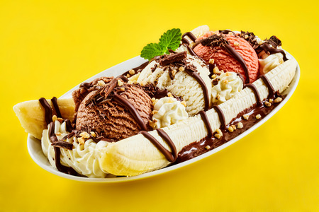 Photo for Tropical banana split with chocolate drizzle over three scoops of chocolate, strawberry and vanilla ice cream on fresh bananas, yellow background - Royalty Free Image