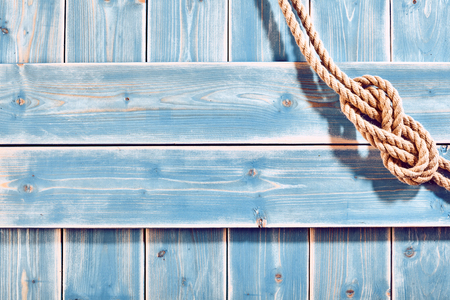 Foto de Nautical Themed Background - High Angle Still Life of Double Figure Eight Knot in Natural Rope Across Corner of Blue Painted Wood Plank Background with Copy Space - Imagen libre de derechos