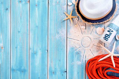 Photo pour Summer vacation beach background theme with seashells, shape of sun in sand, red rope, sun tan bottle and hat with copy space over painted blue wood planks - image libre de droit