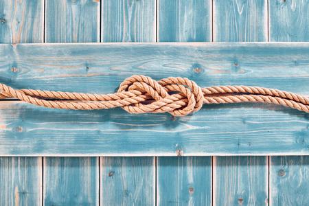 Photo pour Nautical Themed Background - High Angle Still Life of Double Figure Eight Knot in Natural Rope Across Blue Painted Wood Plank Background with Copy Space - image libre de droit