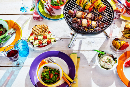 Foto de Overhead Well Laid summer table with colorful dish and plates and brazier on white background with vegan bbq skewers - Imagen libre de derechos