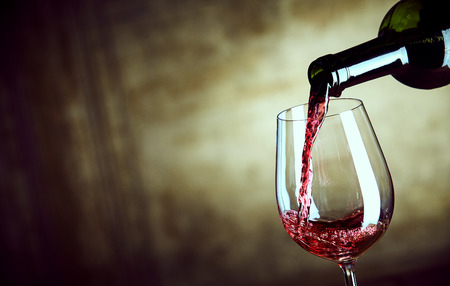 Photo pour Serving a single glass of red wine from a bottle with a close up view of the neck of the bottle and glass over a wide angle abstract brown background with copy space - image libre de droit